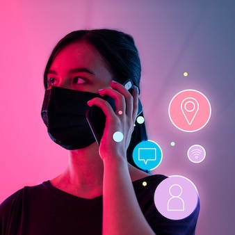 전화로 이야기하는 마스크를 쓰고 사회적 거리를 두는 여성 중 네트워킹