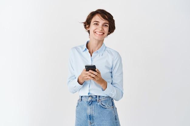 ネットワーキング。白い壁に立っているスマートフォンを保持しているプロの女性の笑顔