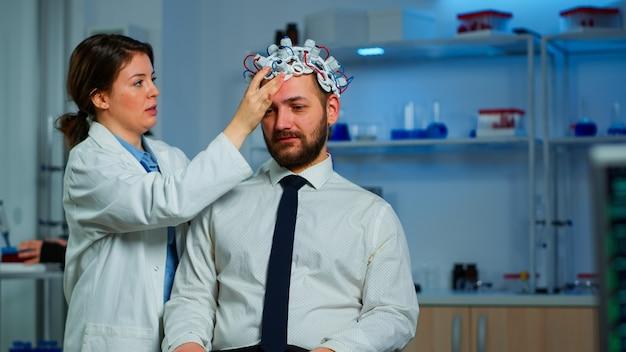 脳波スキャンヘッドセットを使用して人間の脳と神経系を分析する神経内科医。モニター画面で副作用を監視する神経学的イノベーションを開発するハイテクを使用している研究者