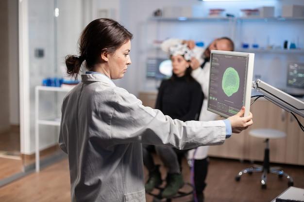 Врач-невролог анализирует сканирование мозга на мониторе в современной исследовательской лаборатории, разрабатывает лекарство для диагностики нервной системы. женщина-пациент в гарнитуре с датчиками