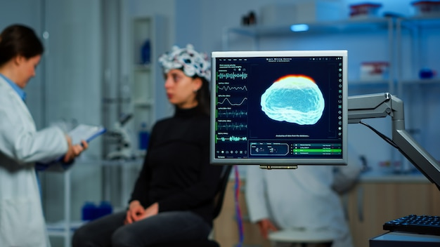 Врач-невролог анализирует нервную систему с помощью наушников eeg, сканирующих головной мозг женщины. ученый-исследователь, использующий высокие технологии, разрабатывает неврологические инновации, отслеживая побочные эффекты на экране монитора