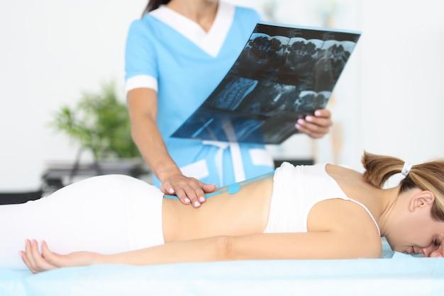 신경과 의사는 파란색 소파에 누워있는 젊은 여자 앞에서 그의 손에 척추 엑스레이를 보유하고 있습니다.