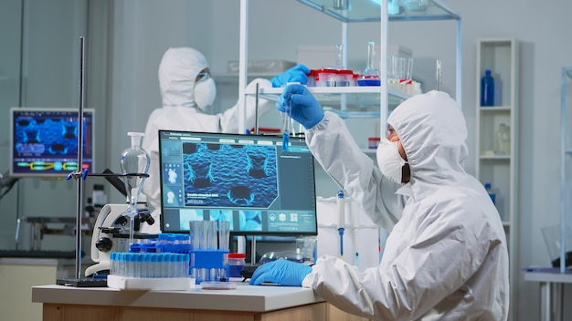 Neurologist with ppe suit working at vaccine development in equipped laboratory typing on pc. team examining virus evolution using high tech for research in treatment development against covid19
