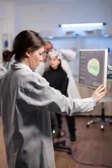 Ученый-невролог изучает сканирование нервной системы мозга на мониторе, машине с датчиками, прикрепленными к пациенту в лаборатории. лаборатория медицины с современной цифровой машиной.