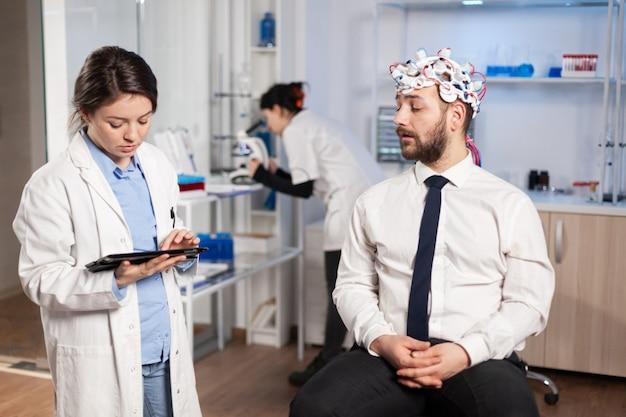 Врач-невролог, использующий планшетный пк для лечения заболеваний головного мозга, объясняет пациенту диагноз болезни. женщина, сидящая в неврологической научной лаборатории, лечит дисфункции нервной системы.