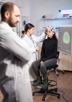 Ученый-невролог настраивает гарнитуру с датчиками на пациентке в современной лаборатории во время сканирования мозга. анализ нервной системы, оборудование для клиник. сканирование мозга доктора.