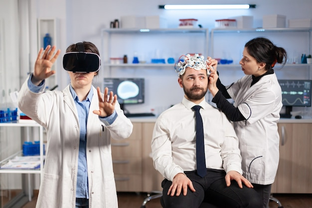 Нейробиолог разрабатывает диагноз в гарнитуре виртуальной реальности в медицинской лаборатории, ассистент настраивает датчики на пациенте, сидящем на стуле. лаборатория медицины с современными технологиями.
