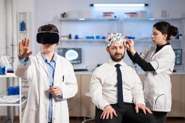 Нейробиолог в гарнитуре виртуальной реальности смотрит на активность мозга пациента и использует высокотехнологичные датчики для сканирования. врач ищет диагноз, эксперимент, eeg, медицинская лаборатория.