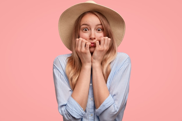 Neurotic beautiful lady in hat and shirt, bites fingernails, stares with fear, feels anxious about something, isolated over pink wall. elegant young woman looks nervously. people and feelings