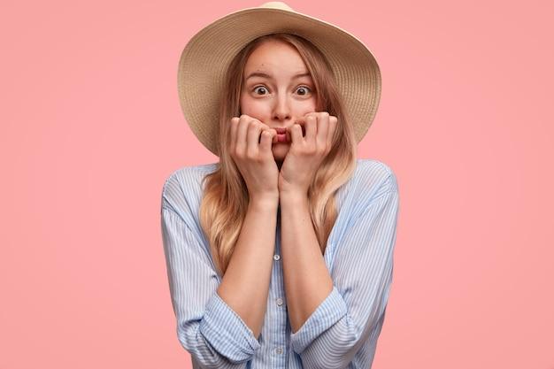 모자와 셔츠를 입은 신경성 아름다운 아가씨는 손톱을 물고 두려움으로 쳐다보고 분홍색 벽 위에 고립 된 무언가에 대해 불안감을 느낍니다. 우아한 젊은 여자가 긴장한 모습. 사람과 감정