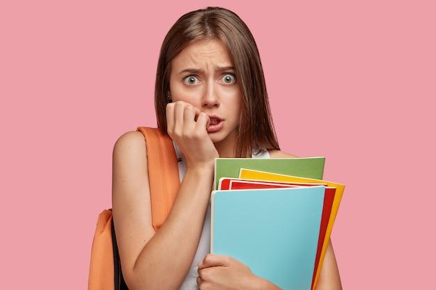 神経症の困惑した学生の女の子が指の爪を噛み、心配そうにカメラを見る