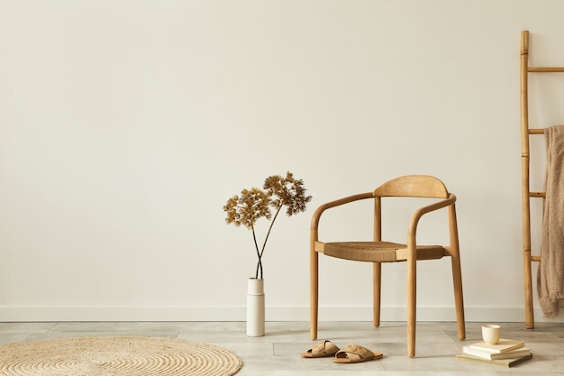 Neutral concept of living room interior with design wooden chair, round carpet, dried flowers in vase, stool, slippers, decoration and elegant personal accessories.. copy space.