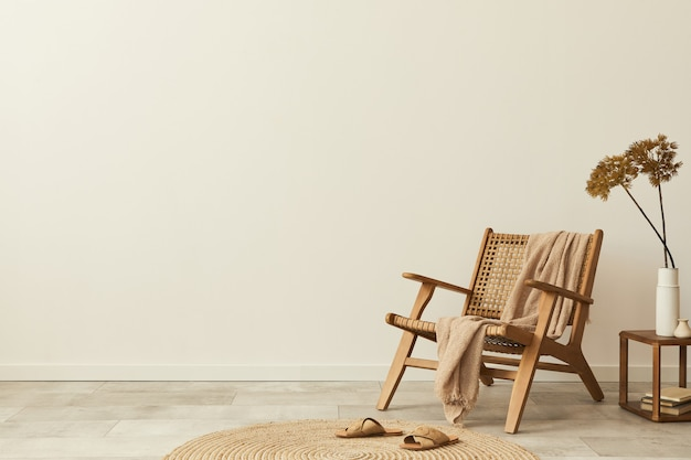 Neutral concept of living room interior with design wooden chair, round carpet, stool, slippers, decoration and elegant personal accessories. template. copy space.