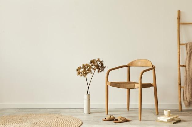 デザインの木の椅子、丸いカーペット、花瓶のドライフラワー、スツール、スリッパ、装飾、エレガントな個人用アクセサリーを備えた、リビングルームのインテリアのニュートラルなコンセプト.コピースペース。