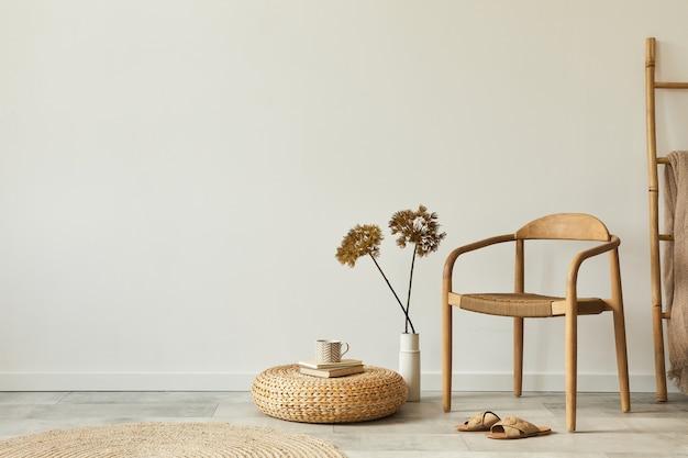 디자인 나무 의자, 둥근 카펫, 꽃병에 말린 꽃, 의자, 슬리퍼가있는 거실 인테리어의 중립 개념