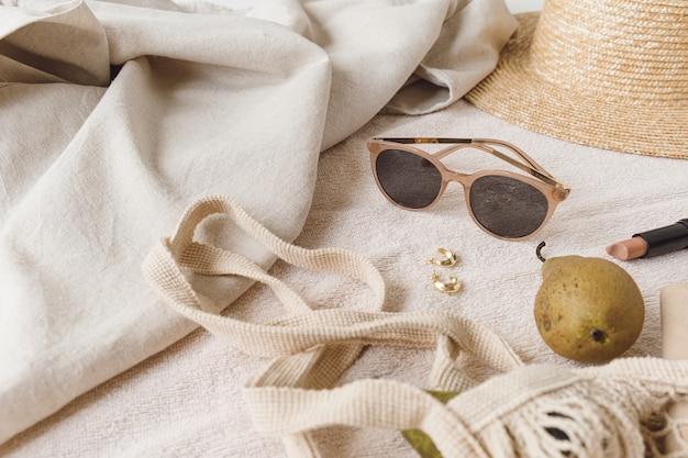 ベージュのブランケットに女性用アクセサリーとジュエリーを組み合わせたニュートラルなファッションコンポジション。ストリングバッグ、麦わら帽子、サングラス、指輪、イヤリング、洋ナシ
