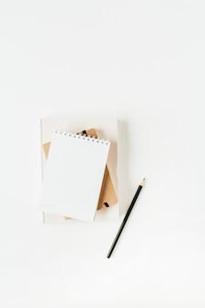 白のノートブックとニュートラルな最小限のオフィスデスクワークスペース