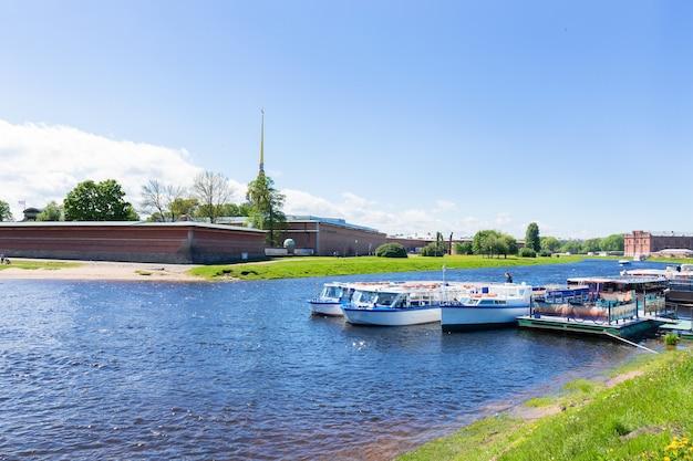 Берег невы, петропавловская крепость и прогулочные туристические лодки. летний солнечный день - санкт-петербург, россия, май 2021 г.
