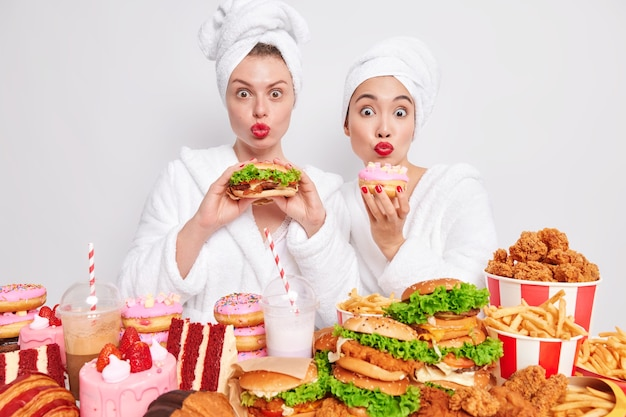 Never enough. two hungry female models in robes consume junk food keeps red lips rounded pose with burger and doughnut stand near table full of cheat meal.