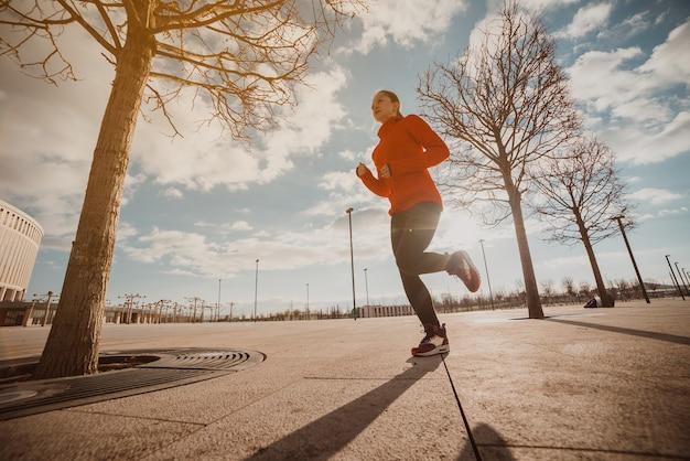 決してあきらめずに動き続けてください!朝日が昇る街を走るスポーツウェア姿の美しい若い女性の全身像。
