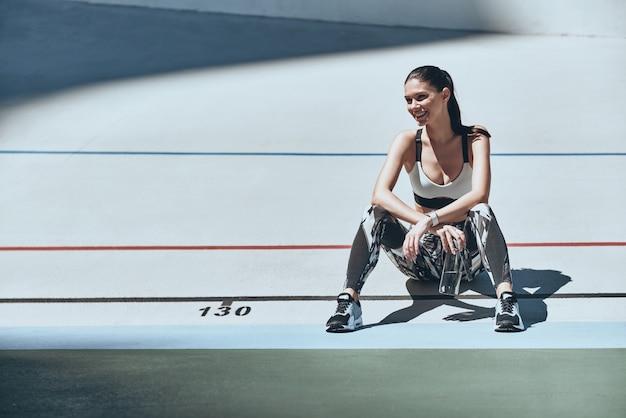 Никогда не сдавайся. красивая молодая женщина в спортивной одежде смотрит в сторону