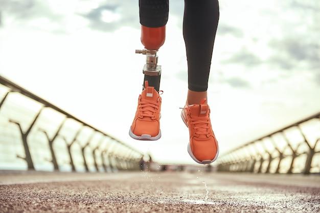 Никогда не сдавайся обрезанное фото женщины-инвалида с протезом ноги в спортивной одежде, прыгающей на