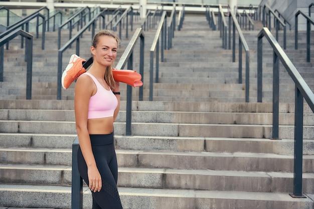 Никогда не сдавайтесь счастливая улыбающаяся женщина в спортивной одежде, держащая протез ноги стоя