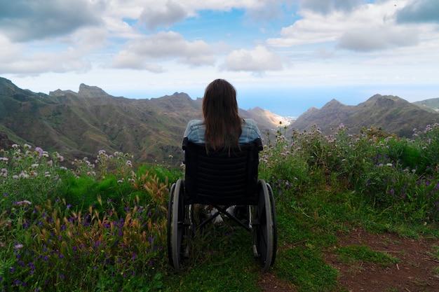 あきらめないで。山の頂上に車椅子に座って、一人旅しながら素晴らしい自然の風景を見ている若い障害者の女性の背面図。国際障害者デー