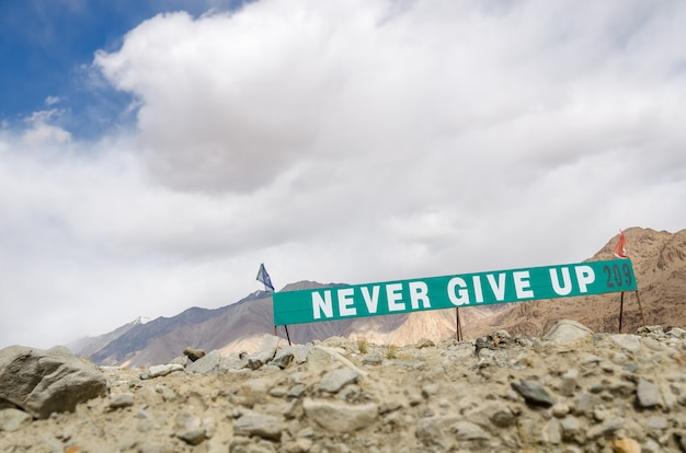 Never give up sign on rough road hill with rock and sandstone mountain