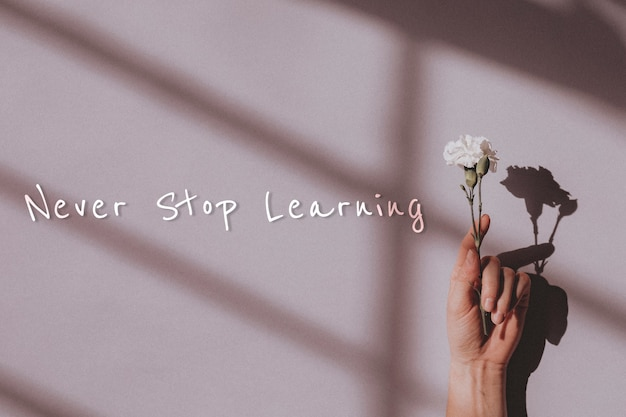 Never stop learning quote and hand holding flower