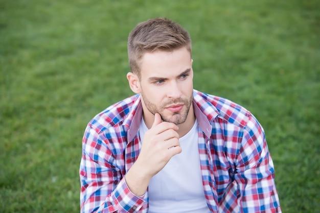 毎日のスキンケアを始めるには若すぎることはありません。若い男は緑の芝生の上に座っています。無精ひげを生やした顔の肌を持つ独身。スキンケア化粧品。適切なスキンケアルーチン。肌の手入れ。メンズスキンケア。