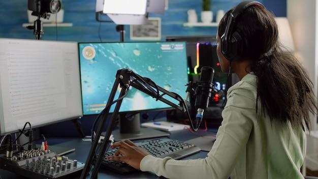 ネバダスな黒いストリーマーがビデオゲームを失い、ヘッドセットでオンラインスペースシューティングゲームをサイバープレイするアフリカの女性のためのゲームオーバー