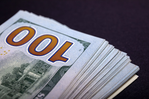 New 100 us dollars 2013 edition banknotes. stack of one hundred dollar bills on a stone table top.