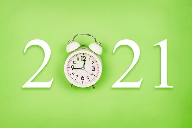 Новый 2021 год с будильником на зеленой поверхности