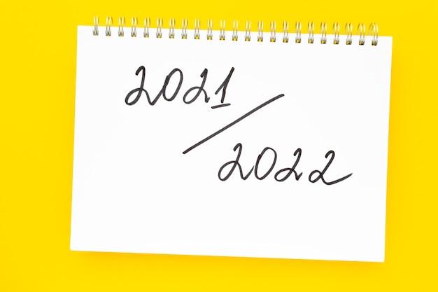 Новый учебный год обратно в школу концепция почерка надпись в белом блокноте на ярко-желтом