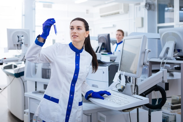 新しい成果。ガラス製品に形成される新しい堆積物を研究しながら、キーボードの上に手を置く賢い陽気な女性科学者