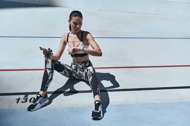 Новое достижение. вид сверху молодой женщины в спортивной одежде, проверяющей шагомер