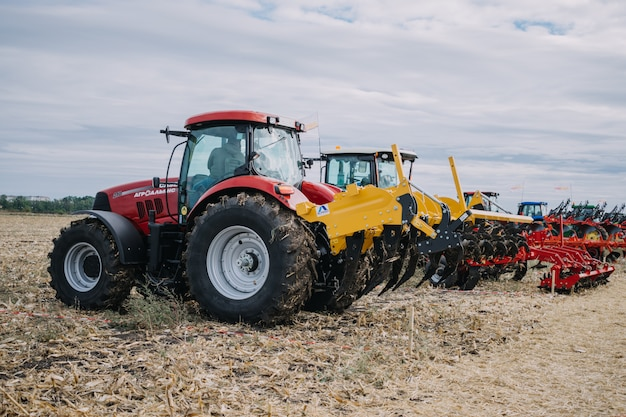 New agricultural machinery, tractors in motion at demonstration field site at agro exhibition