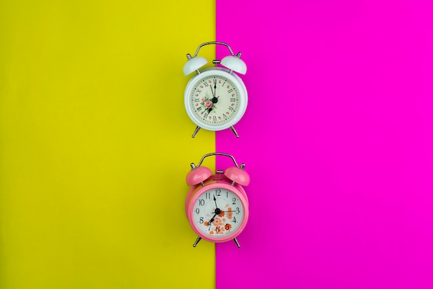 New alarm clock on pink and yellow paper pastel color background