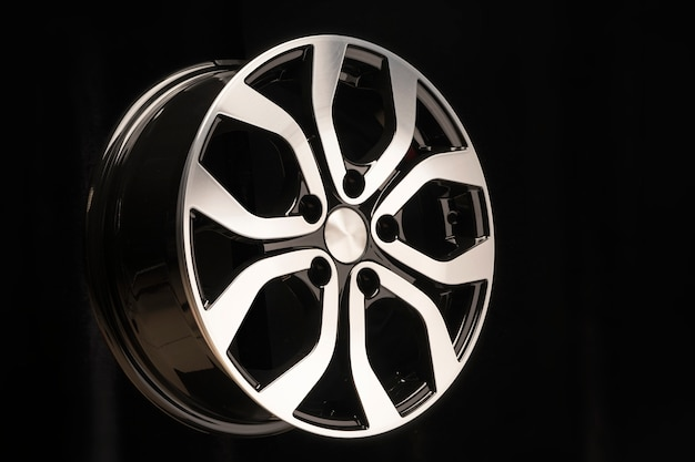 New alloy wheel of the car, close-up on a black space, wheel elements, two-color coating, shiny. left location on the layout