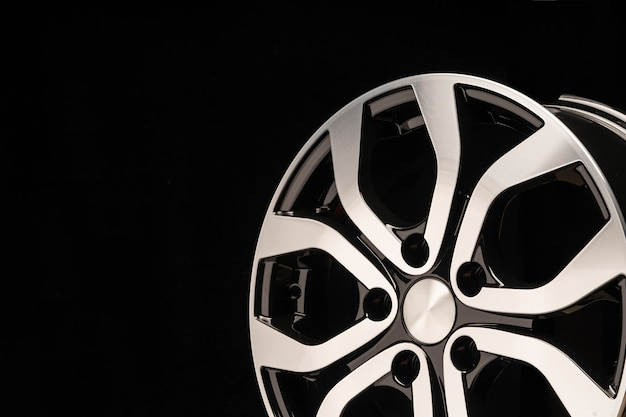 New alloy wheel of the car, close-up on a black wall, wheel spokes. beautiful design. copy space