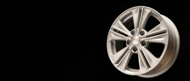 New aluminum alloy wheel, silver color on a black wall. copy space
