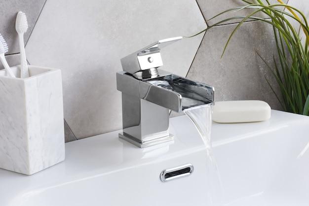 욕실에 세라믹 세면대가 있는 새롭고 현대적인 스틸 수도꼭지 무료 사진