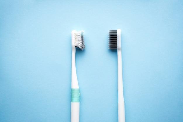 Новые и старые зубные щетки на синем