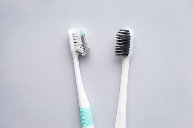 Новые и старые зубные щетки на сером