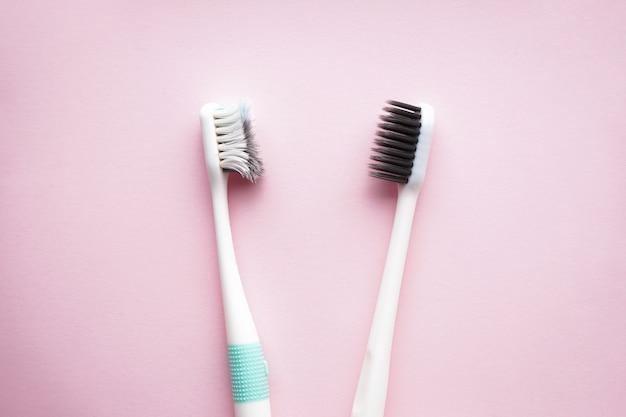 Новые и старые зубные щетки на розовом