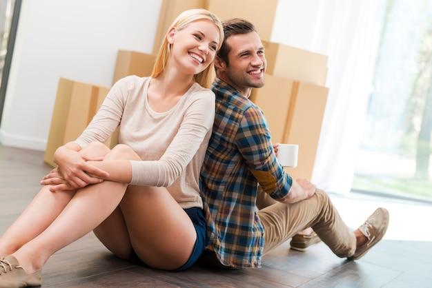 함께 살기 위한 새 아파트. 배경에 판지 상자가 놓여 있는 동안 새 아파트 바닥에 앉아 웃고 있는 젊은 부부