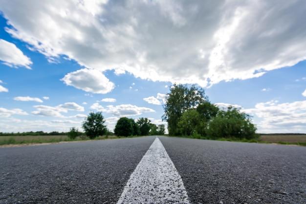 夏に建設された新しいアスファルト道路。高速道路、木々、多くの雲と美しいコントラストの空の美しい風景