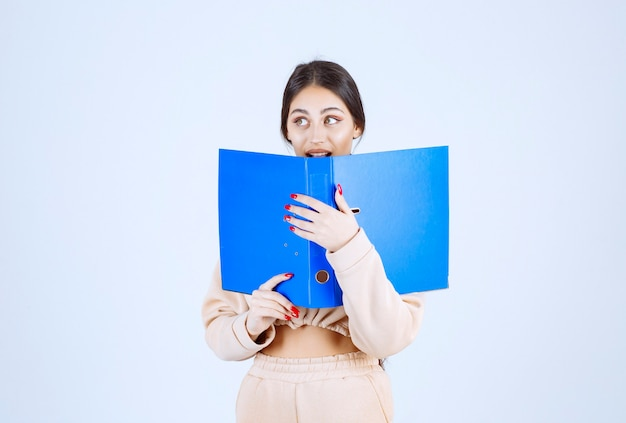 New assistant hiding her face behind a blue folder