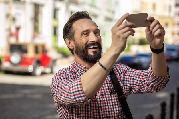 新しいアトラクション。新しい街を発見しながら写真を作って喜んで笑顔の男